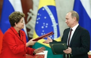 Dilma Rouseff and Vladimir Putin exchanging documents. [AP]