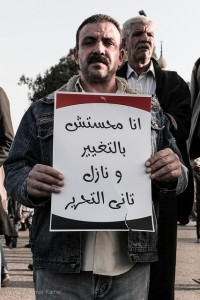"A man holds a sign that reads: ""I'm back in Tahrir cause there's been no change!"". [Omar Kamel]"