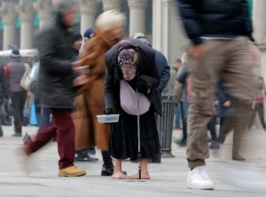 A woman begs for money amid passers by in downtown Milan, Italy. [AP]