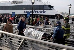 An injured passenger from the Seastreak Wall Street ferry is taken to an ambulance, in New York. [AP]