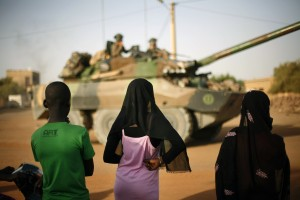 Malian teenagers watch a convoy of French military vehicles pass through Gao, northern Mali [AP Images]