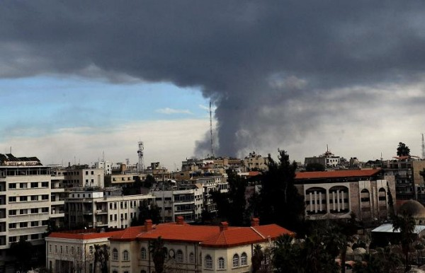 Smoke rises from a building struck by artillery in north Damascus [Xinhua]