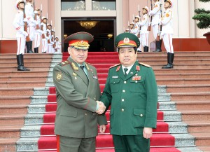 Vietnam's defence minister Phung Quang Thanh (r) shakes hands with his counterpart Sergei Shoigu in Hanoi, Vietnam [Xinhua]