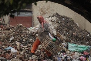 A man sifts through garbage near a market in Cairo as more Egyptians fall on hard times [Getty Images]
