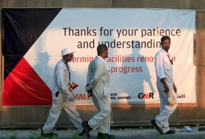 Workers walk past a banner at the international airport in Male, Maldives, Tuesday, Dec 2012. (AP Images)
