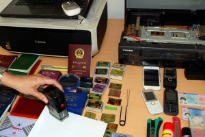Spanish police display items such as fake passports and stamps seized during their raid in Barcelona [AP]