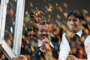 Supporters throw flower petals as Arvind Kejriwal, center, leader of India's Aam Aadmi Party, or Common Man's Party, speaks in New Delhi [AP]