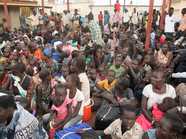 Civilians sit after arriving at the compound of the United Nations Mission in the Republic of South Sudan (UNMISS), adjacent to Juba International Airport, to take refuge from the fighting [AP]