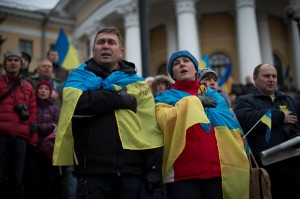 Ukrainians wearing national flags sing the national anthem during a pro-European Union rally in Independence Square in Kiev, Ukraine, Sunday, Dec. 15, 2013 [AP Images]