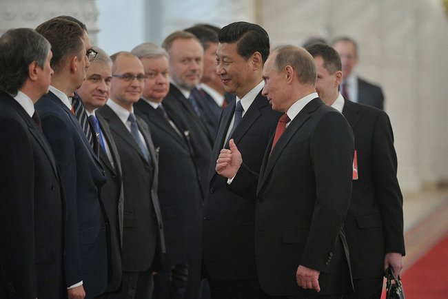 Putin (right) presents the Russian delegation to President of China Xi Jinping in March last year [PPIO]