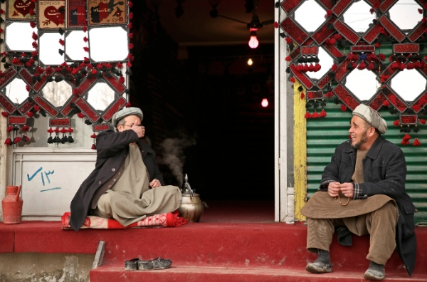Afghan shopkeepers chat as they wait for customers, in front of their carpet shop in Kabul, Afghanistan, Monday, Jan. 13, 2014. With millions of dollars in foreign aid flooding into the country, many Afghans still live in poverty [AP]