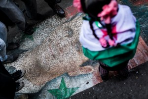 Syrian opposition suppoerters stomp on a portrait during a demonstration in the neighborhood of Bustan Al-Qasr, Aleppo, Syria, Friday, Jan. 4, 2013 [AP]