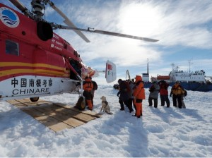 Passengers from the trapped Russian vessel MV Akademik Shokalskiy, seen at right, prepare to board the Chinese helicopter Xueying 12 in the Antarctic Thursday, Jan. 2, 2014 [AP]