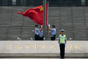 Chinese police officers raise the national flag outside the Jinan Intermediate People's Court in Jinan in eastern China's Shandong province [AP]