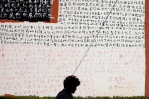 "A woman walks past a wall covered with Chinese characters from chapters of John Rawls' book ""A Theory of Justice"" outside an art gallery in Beijing [AP]"
