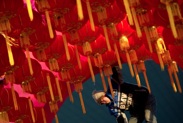 A worker installs a Lunar New Year decoration outside a shopping mall in Beijing Wednesday, Jan. 15, 2014 [AP]