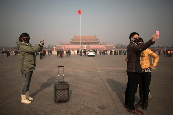 Tourists in masks use mobile phone cameras to snap shots of themselves during a heavily polluted day on Tiananmen Square in Beijing, China, Thursday, Jan. 16, 2014. [AP]