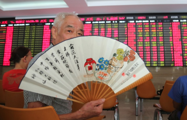 An investor cools off with a fan at a private securities company in Shanghai, China [AP]