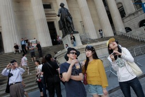 A group of tourists from China take in the sights of the New York Stock Exchange and Federal Hall National Memorial. Major hotel brands are bending over backward to cater to the needs of the world's most sought-after traveler: the Chinese tourist [AP]