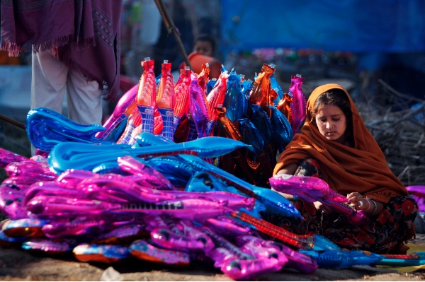 An Indian woman vendor sells guitar-shaped balloons during a fair at Kanachack village, outskirts of Jammu, India, Nov.18, 2013 [AP]
