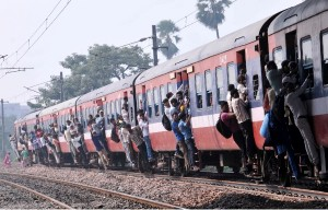 Indian passengers hang from the doors of the coaches of an over crowded train [AP]