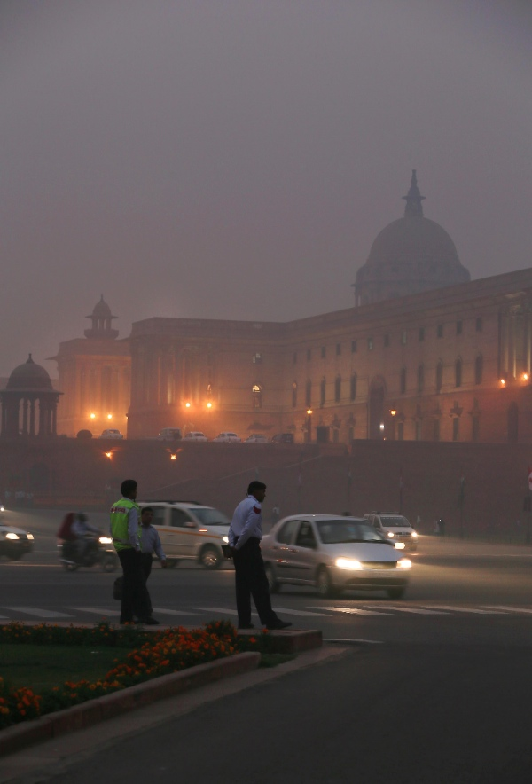 Traffic policemen monitor traffic in front of the Presidential Palace enveloped by a blanket of smog in New Delhi [AP]