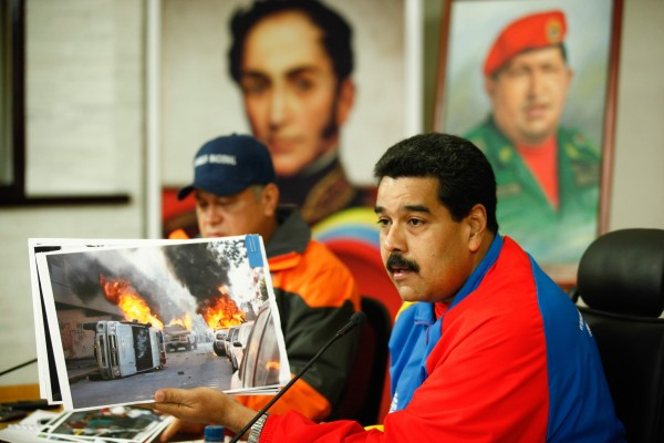 Maduro holds up an image of street violence adding that the opposition and Washington have been inciting the protests [Xinhua]