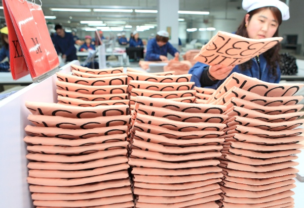 A worker packs garments for export in Jifa Group in Jimo City, east China's Shandong Province, Feb. 6, 2014. China's foreign trade volume climbed 10.3 percent year on year in January to 382.4 billion U.S. dollars [Xinhua]