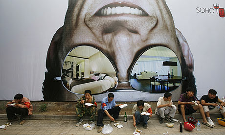 Workers eat their lunch in front of a billboard which promotes a new residential complex in Beijing, China. File Photo [AP]