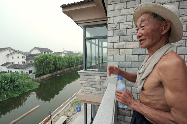 A villager takes a rest at the balcony of his new house at Nanxun Township in Huzhou City, east China's Zhejiang Province [Xinhua]