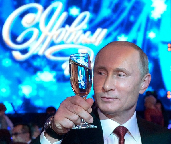 "Russian President Vladimir Putin, toasts during a New Year dinner in Khabarovsk, Russia's Far East, Tuesday, Dec. 31, 2013, with a neon sign behind declaring ""Happy New Year"" [AP]"