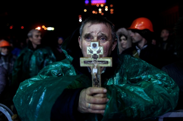 An anti-government protester holds a crucifix as he prays at Independence Square in Kiev, Ukraine, Thursday, Feb. 20, 2014 [AP]