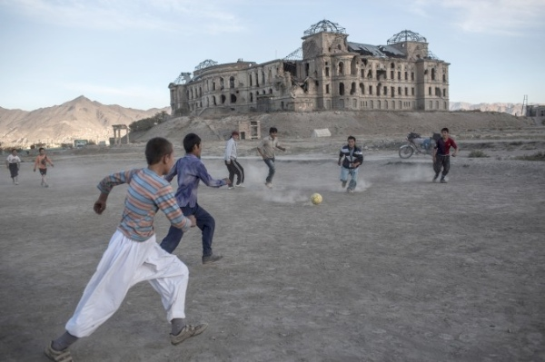 Afghan children play soccer in front of the ruined Darul Aman Palace in Kabul, Afghanistan, Nov. 8, 2012 [Getty Images]