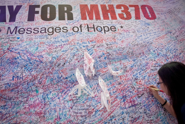 A woman leaves a messages of support and hope for the passengers of the missing Malaysia Airlines MH370 in central Kuala Lumpur March 16, 2014 [Xinhua]