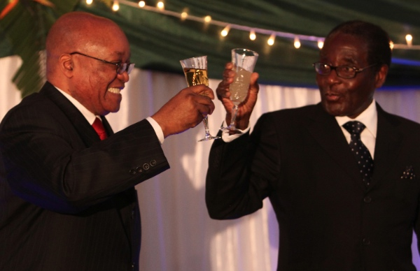 File photo of Zimbabwean President, Robert Mugabe, right, giving a toast to visiting South African President, Jacob Zuma, left, during a state banquet hosted in Harare [AP]