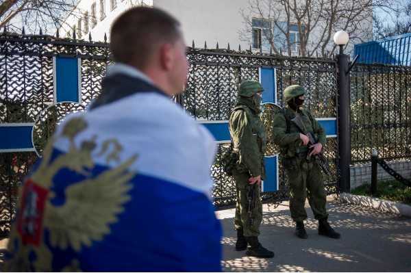 A pro-Russian man wearing the Russian national flag walks past an entrance to the General Staff Headquarters of the Ukrainian Navy in Sevastopol, Ukraine, Monday, March 3, 2014 [AP]