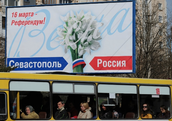 "People ride in a bus by a poster reading ""March 16 - Referendum! Sevastopol. Russia"" in Sevastopol, Thursday, March 13, 2014 [AP]"