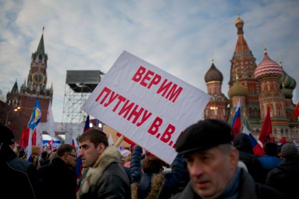 "A Pro-Putin demonstrators holds posters reading ""We Believe Putin!"" as others gather towards to Red Square in Moscow, Russia, Friday, March 7, 2014, with Spassky Tower, left, and St. Basile Cathedral, right, are in the background [AP]"