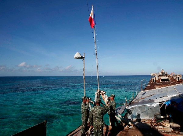 Philippine Marines raise the Philippine flag on the first day of their deployment on the dilapidated navy ship LT57 BRP Sierra Madre at the disputed Second Thomas Shoal, locally known as Ayungin Shoal, Sunday, March 30, 2014 off the South China Sea [AP]