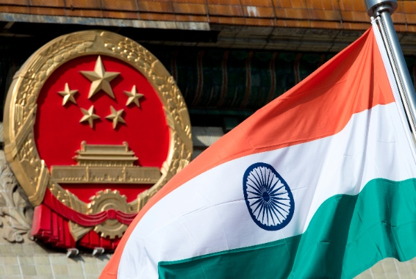 An Indian national flag is flown next to the Chinese national emblem during a welcome ceremony for visiting Indian Prime Minister Manmohan Singh, outside the Great Hall of the People in Beijing Wednesday, Oct. 23, 2013 [AP]