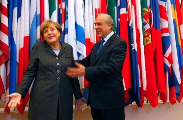 Head of the Organization for Economic Co-operation and Development (OECD) Angel Gurria, centre, and Germany's Chancellor Angela Merkel, react, prior to their meeting at the OECD headquarters in Paris, Wednesday, Feb. 19, 2014 [AP]