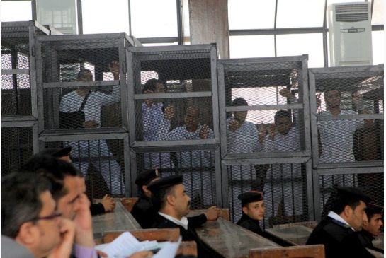 In this file photo taken Wednesday, March 5, 2014, Al Jazeera English bureau chief Mohamed Fahmy, left, producer Baher Mohamed, second left, and correspondent Peter Greste, center, stand inside the defendants' cage in a courtroom during their trial on terror charges, along with several other defendants, in Cairo Egypt [AP]