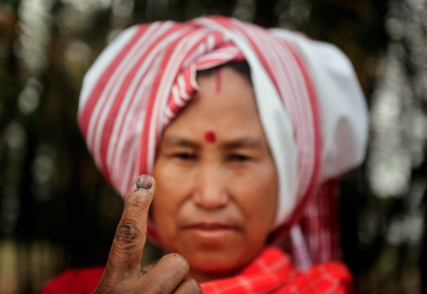 A Mishing tribal woman displays her indelible ink mark on her finger after casting her vote outside a polling station during the first phase of elections at Misamora Sapori, an island in the River Brahmaputra in the northeastern Assam state, India, Monday, April 7, 2014 [AP]