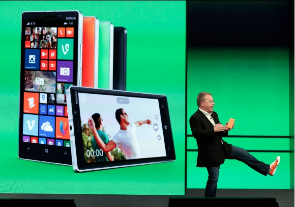 Stepen Elop, executive vice president of Nokia shows off his colored shoe while talking about the colors available of the new Nokia Lumia 930 phones during a keynote address at the Microsoft Build Conference Wednesday, April 2, 2014, in San Francisco [AP]
