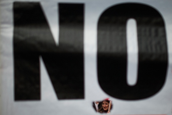 "A protestor is seen though a banner reading ""No"" as she marches during a protest against government's austerity measures in Madrid, Spain, Thursday, April 3, 2014 [AP]"