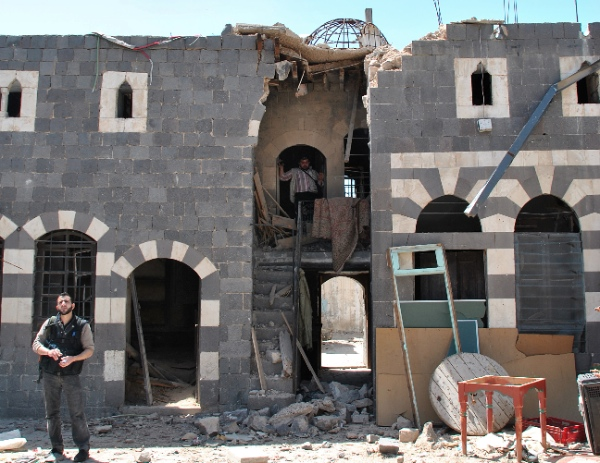 In this Friday, April 20, 2012 file photo, a Syrian rebel stands inside a damaged historic house that was shelled by the Syrian security forces, at al-Hamidiya neighborhood, in the old city of Homs province, central Syria [AP]