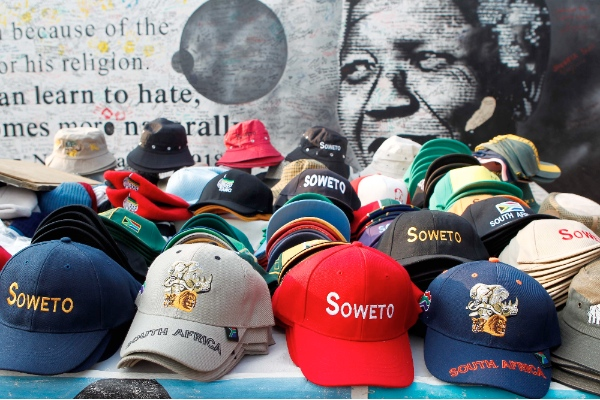 Photo taken on May 6, 2014 shows souvenirs on display in front of a poster of late South African President Nelson Mandela, in Soweto, Johannesburg, South Africa [Xinhua]