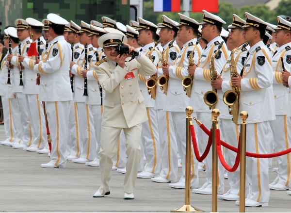 A Russian naval officer takes pictures during the welcome ceremony at a naval port in Shanghai, east China, May 18, 2014 [Xinhua]