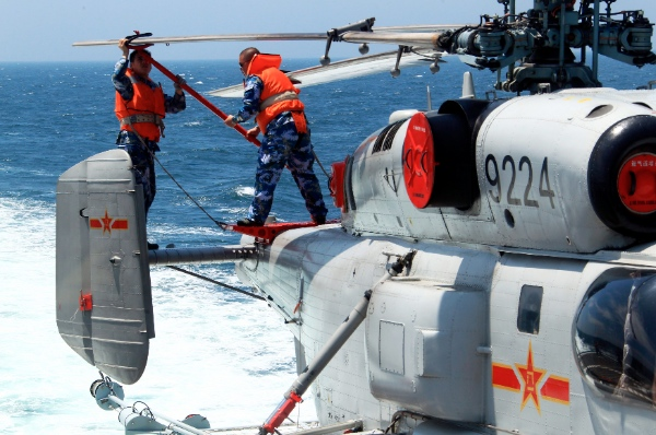 Chinese navy soldiers work on a helicopter before sending it into hangar on China's Zhengzhou missile destroyer during the China-Russia joint naval drill on East China Sea, May 24, 2014 [Xinhua]