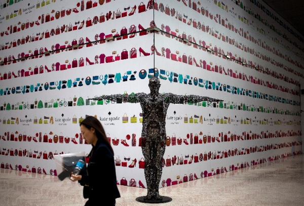 A woman walks past an art sculpture on display in front of an under construction fashion boutique outlet covered by its advertisement board at a shopping mall in Beijing, China Monday, May 12, 2014 [AP]